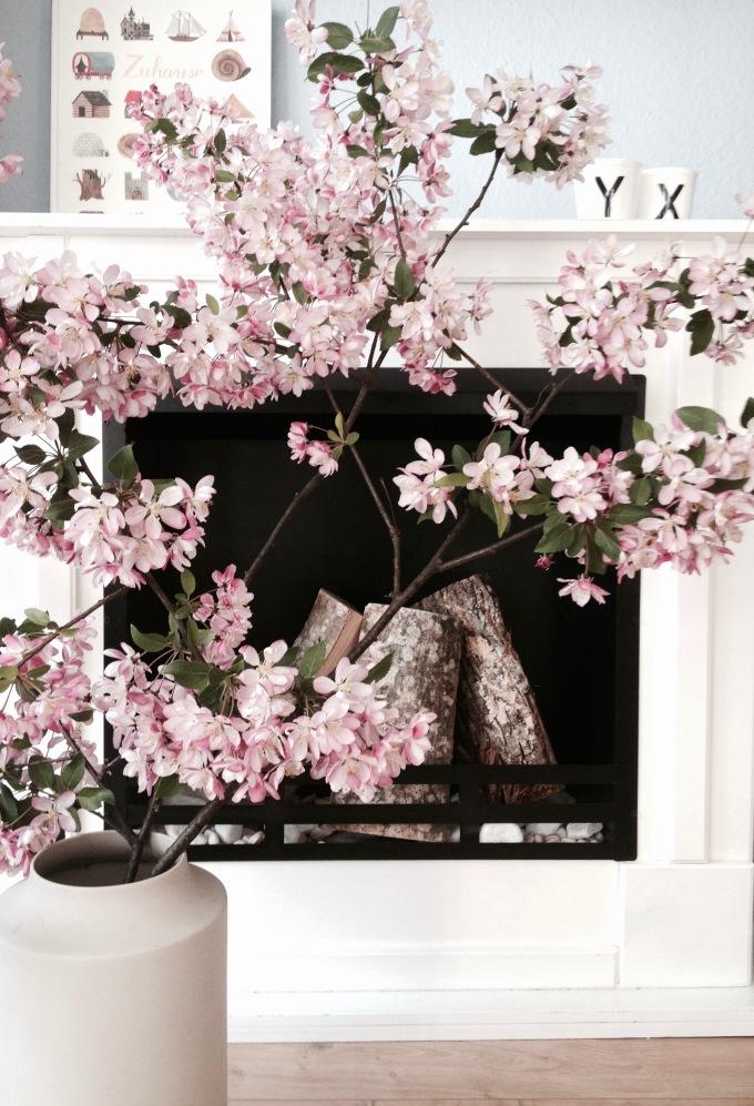 Kamin mit Kirschblütenzweigen